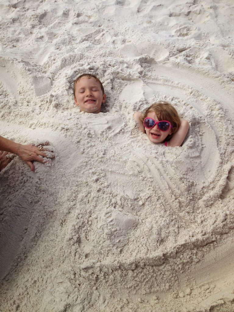 kids buried in the sand