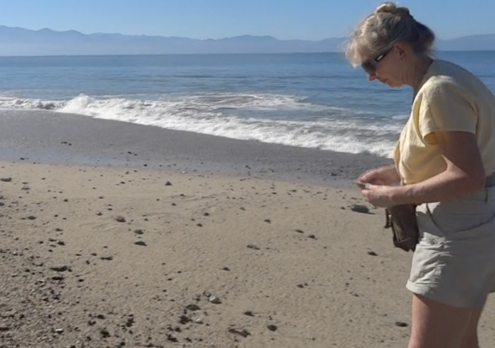 Sue looks for sea glass on Bucerias Beach Mexico